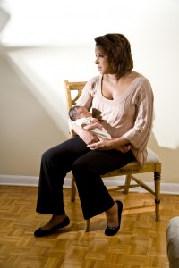 African American mother with sad expression holding newborn